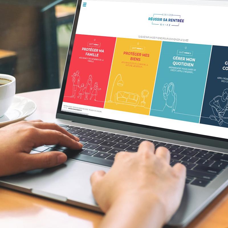 Personne dans un café avec le mains posées sur le clavier d'un ordinateur portable ouvert sur le site internet de Banque Populaire